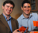 Photo of Marc Baldo and Shalom Goffri of MIT holding examples of organic solar concentrators.