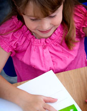 Photo of a young girl using a ruler on a piece of paper.