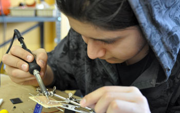 Photo of a student soldering together a solar-powered robot.