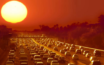Photo of sun radiating over highway filled with cars in traffic in Phoenix
