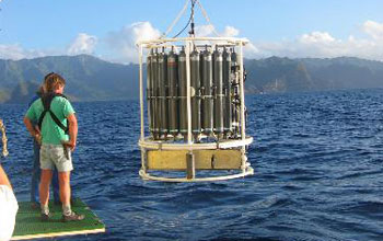 Photo of a researcher on a research vessel watching seawater sampling equipment.