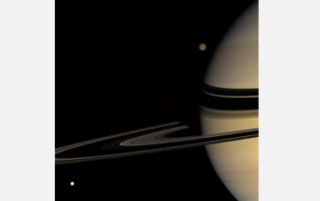 Image shows Titan at the top emerging from behind Saturn and Tethys at the bottom left.