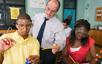 Photo of a teacher with two students carrying out a science experiment.