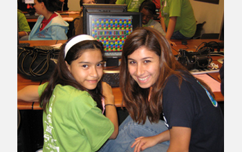 Photo of a student demonstrating a computer game she developed to another student.