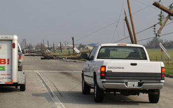 Photo of vehicles traveling down a road with downed telephone poles and collapsed houses.
