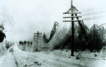 Photo of a snow-covered road and telephone wires sagging under a heavy burden of snow.