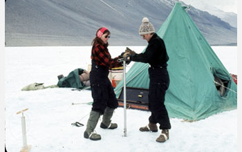 Photo of women geoscientists using a hand augur to drill Lake Vanda, Antarctica, in 1969-1970.
