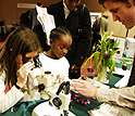 photo of students looking through a microscope at the plant modeling exhibit