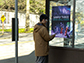 a man with his smartphone at a bus stop looking at a poster