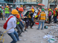 volunteers remove debris from a collapsed building