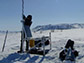 researcher sitting out microphones in the foothills of Alaska's Brooks Range