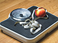 image of a scale with a tape measure and an apple on it